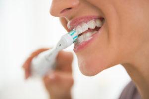 Joven chica cepillándose los dientes con un cepillo eléctrico